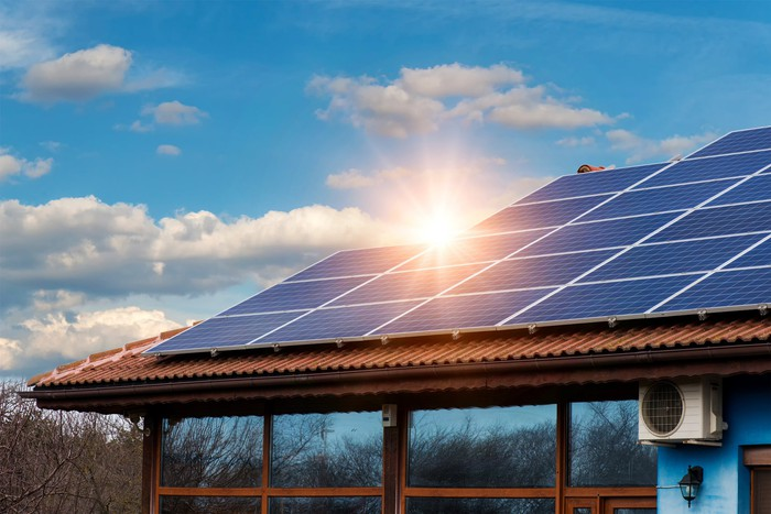 Solar panels on the roof a home with the sun low in the sky