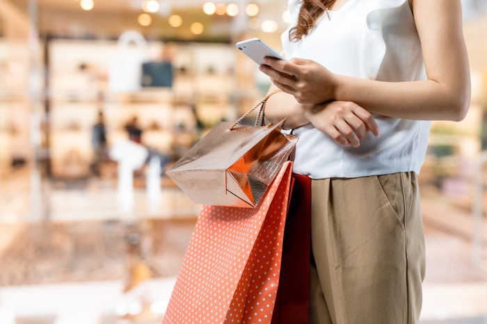 Woman holding multiple shopping bags and smartphone.