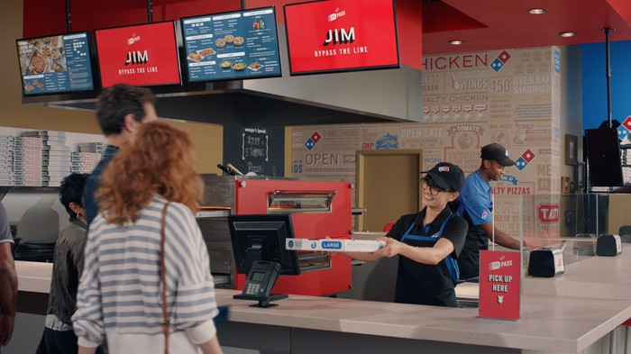 A Domino's employee hands an order to a customer.