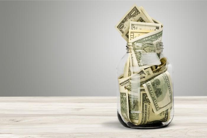 A glass jar full of dollar bills of various denominations