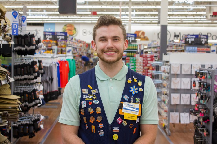 A Walmart sales associate standing in the store smiling.