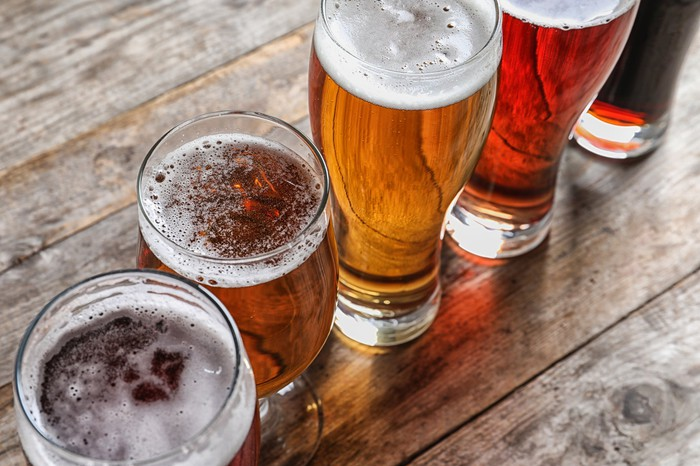 Photograph of various glasses of beer on a bartop.
