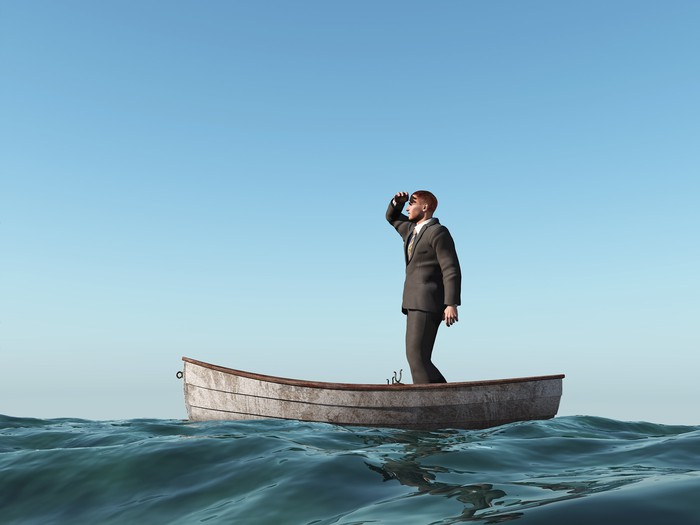 A businessman standing up in a small boat at sea peering out into the distance.