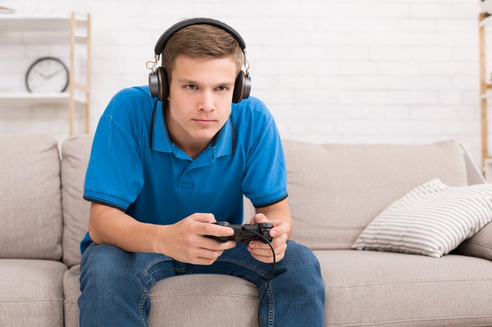 Photograph of young man playing video games while sittng on a couch.