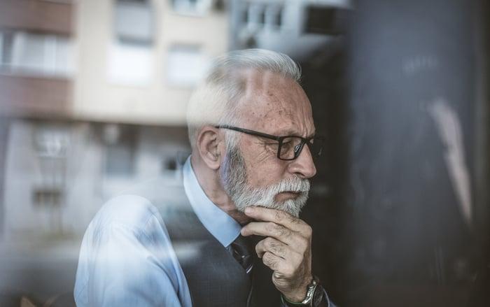 Older man resting chin on hand.