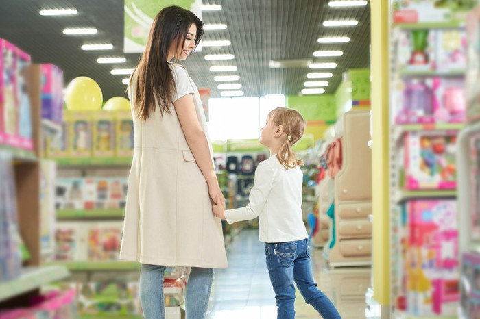 A mother and daughter holding hands inside a toy store