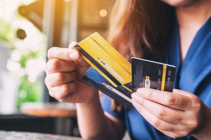 Closeup of a woman's hands shuffling through several credit cards.