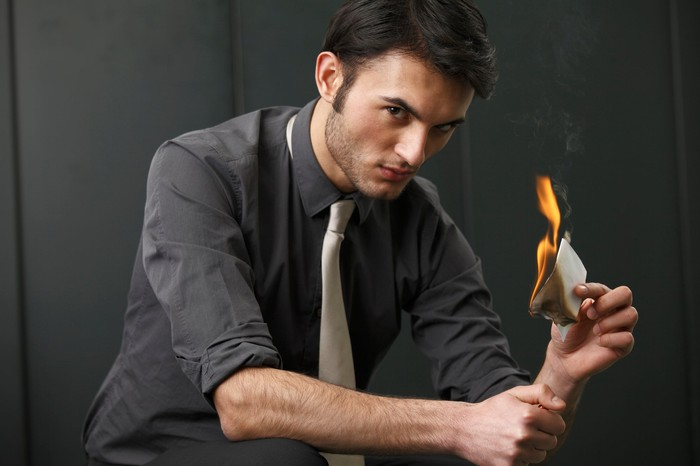 A young businessman glares at the camera, holding a lighter in one hand and a burning piece of paper in the other.