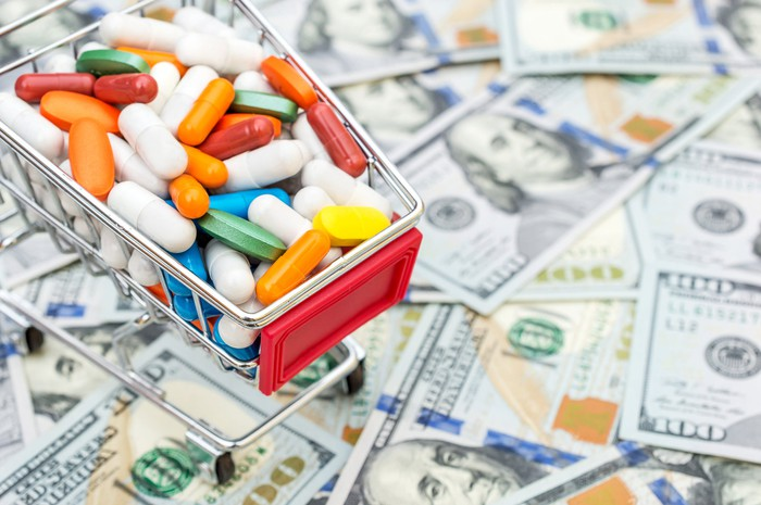 A miniature shopping cart filled with a colorful array of pills sits atop a scattered pile of hundred dollar bills.