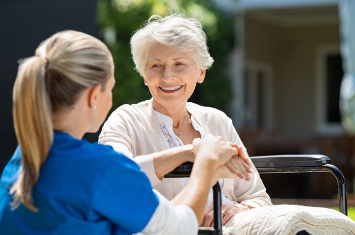 Seated outdoors, a healthcare provider speaks with a smiling older woman.