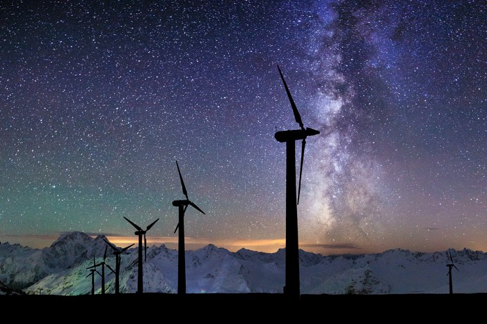Silhouettes of wind turbines in front of a starry background.