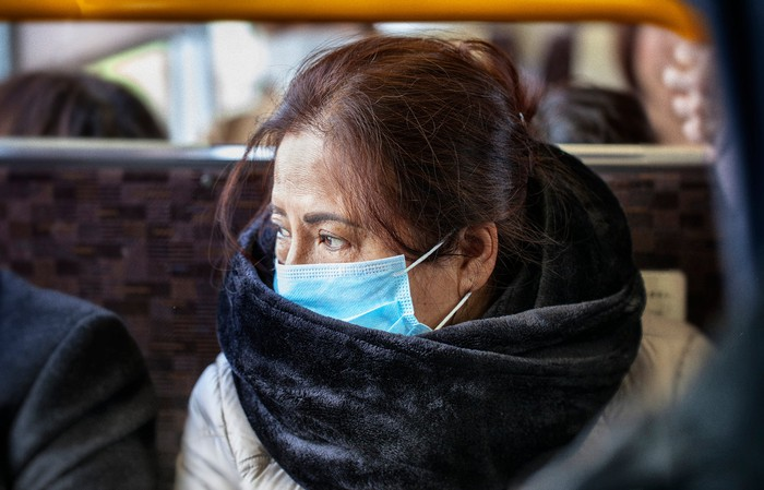 Asian woman wearing surgical mask on a bus