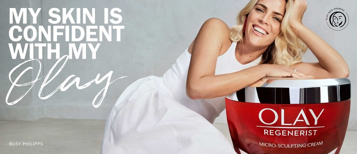 Actress Busy Philipps in an ad for Olay Regenerist skin cream, along with the brand's 'Skin Promise' mark and the text 'My skin is confident with my Olay.'