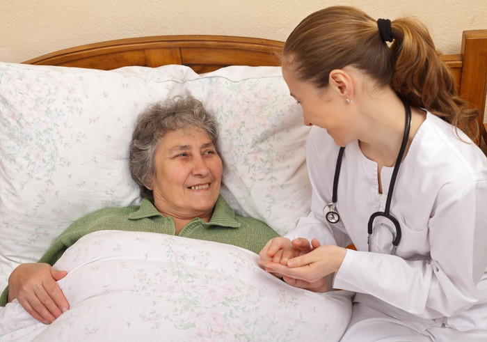 Nurse holding the hand of a smiling senior citizen who is lying in bed