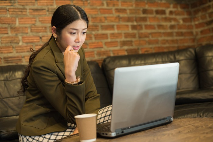 Woman at laptop sitting on couch in front of brick wall.
