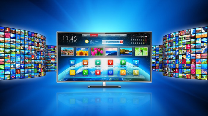 A connected TV showing viewing options and apps, with walls of television screens on either side.