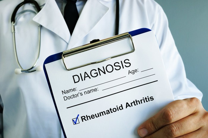 "A doctor holds a chart that says: ""Diagnosis: rheumatoid arthritis"""