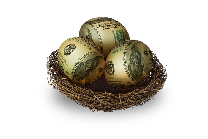 A nest containing three eggs painted to look like hundred dollar bills