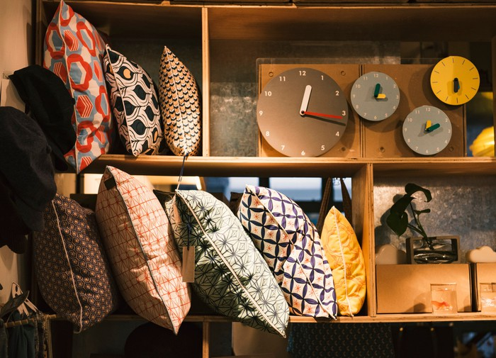 A shelf with pillows and clocks at home goods store