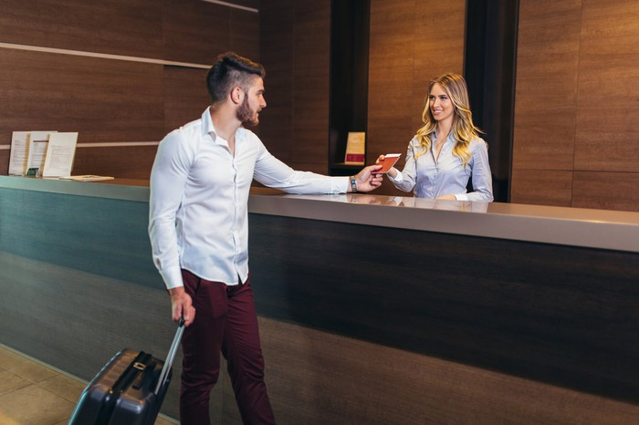 A young man checks into a modern hotel in the lobby.