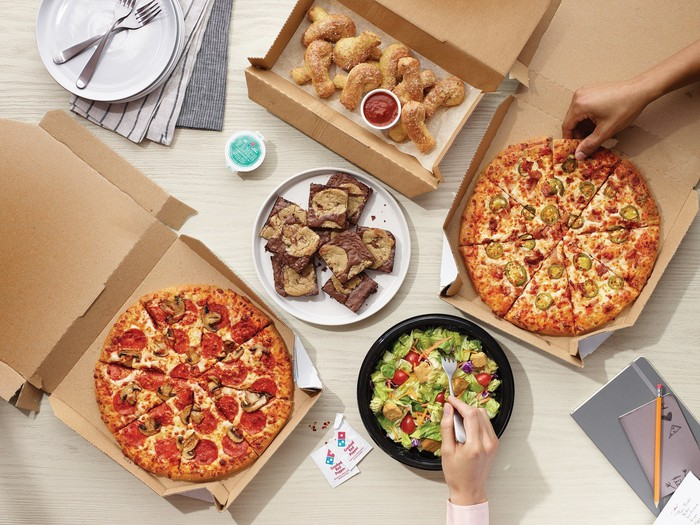 A table with pizzas, utensils, and other items.