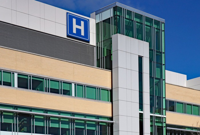 Hospital building with a big white H in a blue square on the side of it.