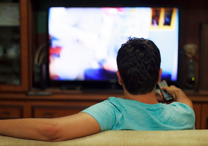 A man sitting on a couch watching TV as seen from behind.