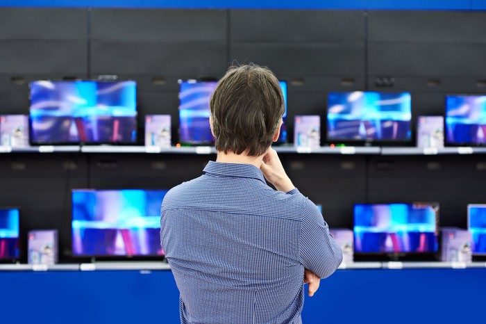 A man with his back turned is watching a bunch of TVs.