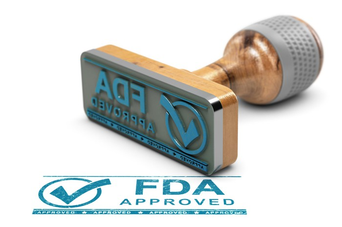 A rubber stamp that stamps FDA approved with a checkmark.