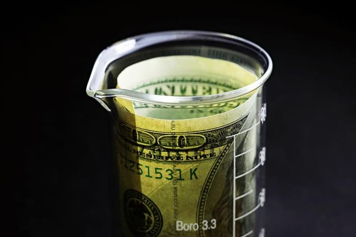 A one hundred dollar bill in a beaker.