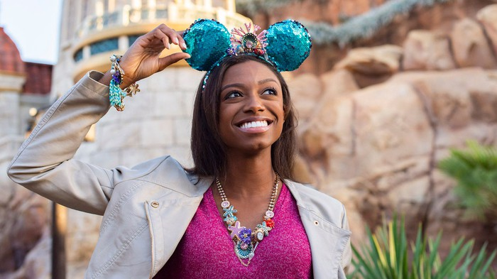A woman wearing Mickey Mouse ears at a Disney theme park.