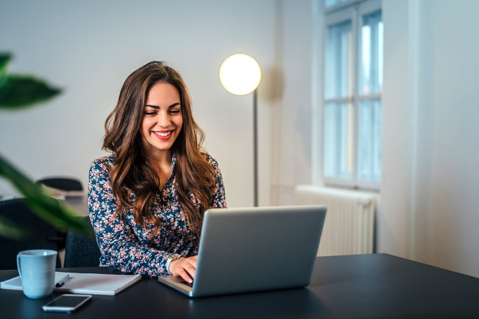 Smiling woman at laptop with small lamp pointed at her from behind