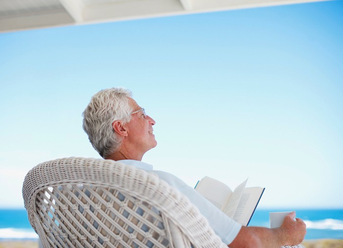 Older man in wicker chair reading book, holding mug, and facing the ocean