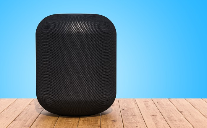 Apple's HomePod on a wood table.