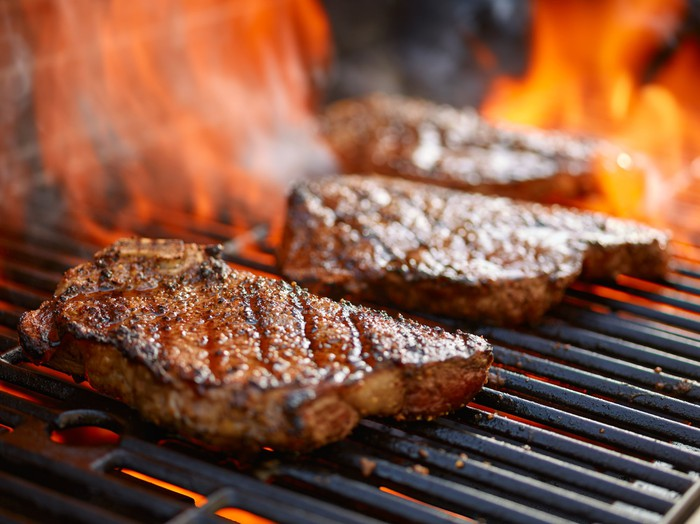 Three steaks cooking on a grill