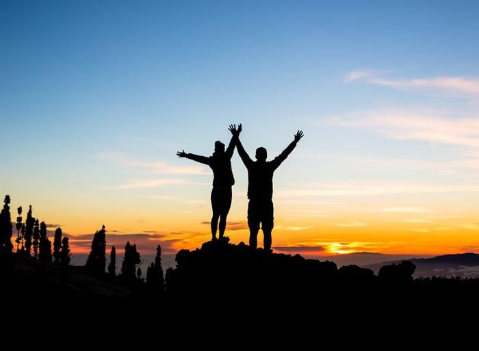 Couple celebrate reaching a mountain summit.