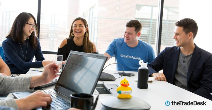Smiling co-workers gathered around a conference table, with one wearing a t-shirt with The Trade Desk logo.