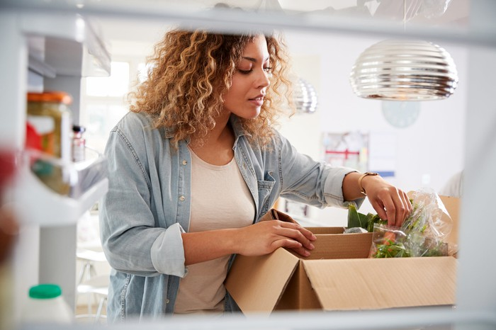 A woman looks into a box containing her grocery delivery as she stands in her kitchen.