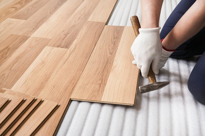A person installing wood flooring