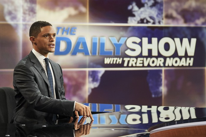 Daily Show host Trevor Noah sitting at a desk.