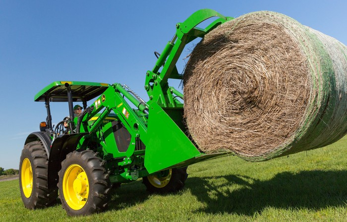 Green tractor carrying a hay bale across a green lawn.