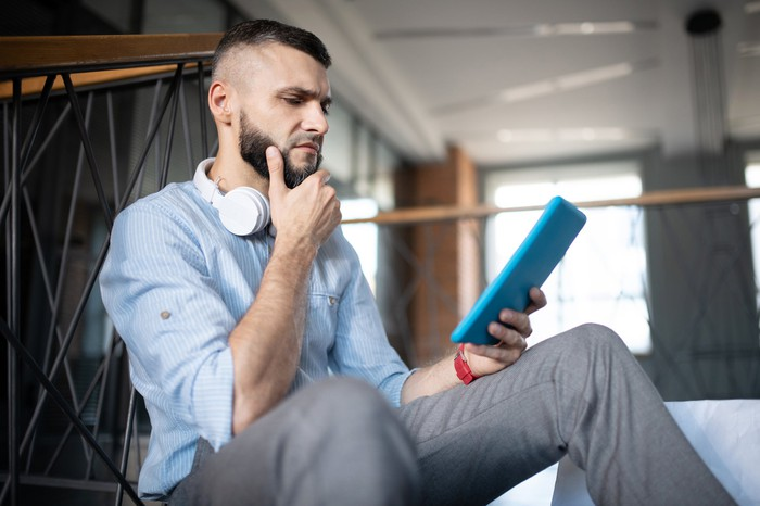 Young man sitting and stroking beard while holding tablet and sporting worried look on face