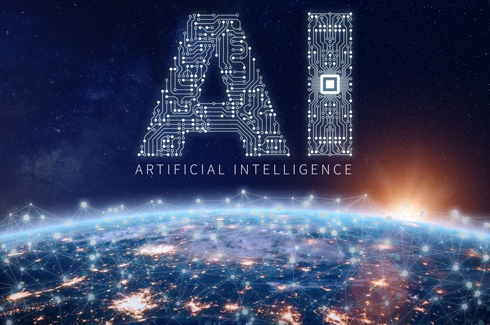 The letters AI over the words artificial intelligence, with the earth and city lights beneath.