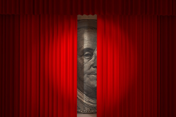 A very large $100 bill peeks out between two red curtains, with a spotlight focused on Benjamin Franklin's face.