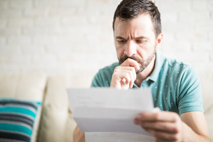 Man with serious expression resting hand on chin while looking at document
