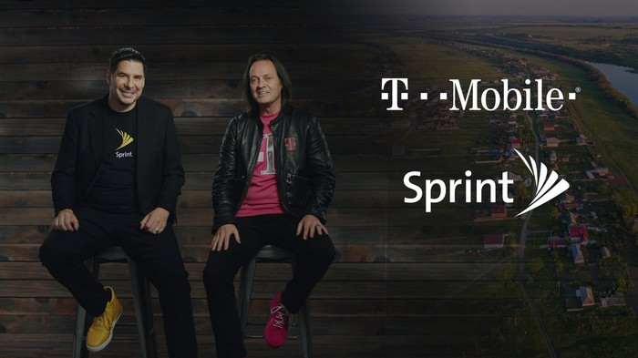 John Legere and Marcelo Claude sitting next to T-Mobile and Sprint logos