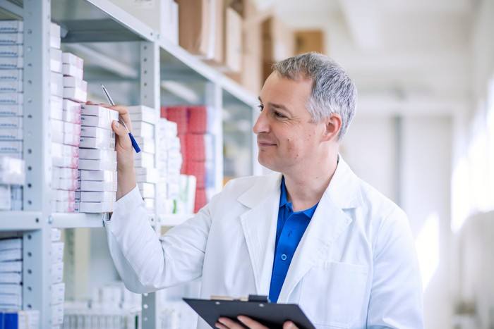 A gray-haired pharmacist holding a clipboard as he takes inventory.