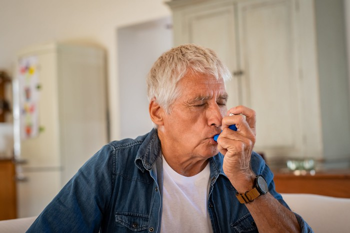 Senior man using an inhaler