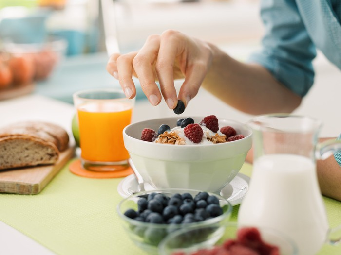 A woman's hand adds a blueberry to a bowl of healthy cereal on a table with milk, juice and a bowl of blueberries.