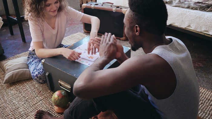 Young couple sitting on carpet playing board game.